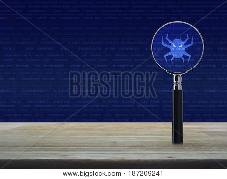 Virus computer icon with magnifying glass on wooden table over binary code background Business internet security concept
