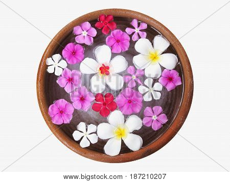 White plumeria and pink flowers floating on water in ceramic pottery for spa isolated on white background.