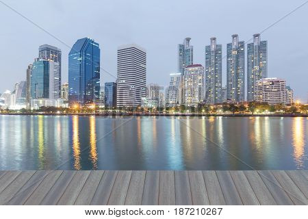 Opening wooden floor Office building with water reflection with twilight background cityscape background