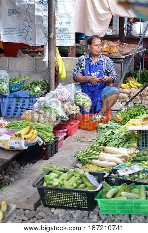 MAE KLONG THAILAND- MAY 17 2017: Vendors sell food at Mae Klong railway tracks market in Thailand. The market is notable for its location on active railroad line