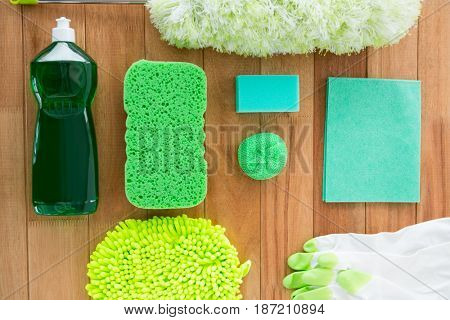 Overhead view of sponge with duster and bottle on wooden table