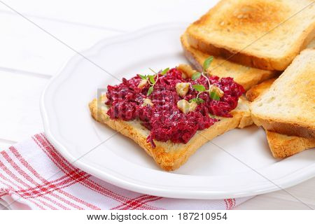 toasts with fresh beetroot spread on white plate - close up