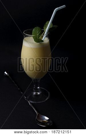 Cocktail of piña colada with mint next to cocktail accessories on a black background