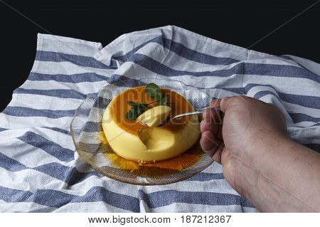 Man taking a teaspoon a piece of vanilla custard served in a glass dish on a dishcloth