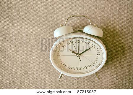 Retro alarm clock on a bed Photo in retro color image style