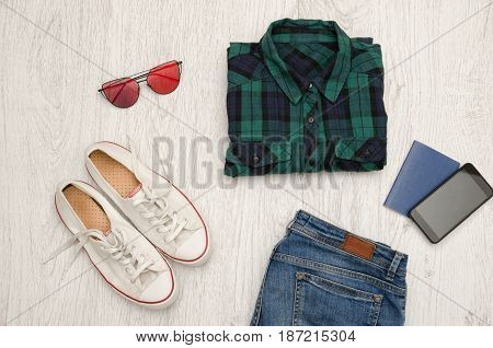 Blue-green Checkered Shirt, Glasses, Sneakers, Jeans, Phone And Passport. Wooden Background. Fashion