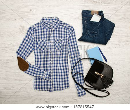 Blue And White Plaid Shirt, Jeans, Mobile Phone, Notebook With Pen And Black Bag. Wooden Background.