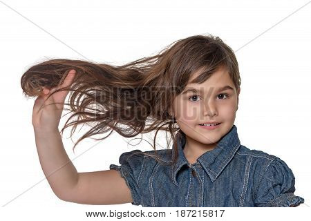 Portrait of cool brunette long haired little girl holding her hair isolated on the white background.