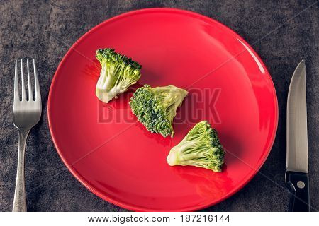 Broccoli on the plate red. Fork and knife. Concept - vegetarianism weight control diet healthy eating.