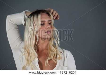 Close up of transgender young female standing against gray background