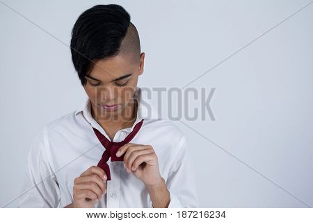 Transgender woman tying necktie while standing against white background