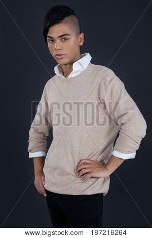 Portrait of transgender woman with hands on hip standing against gray background