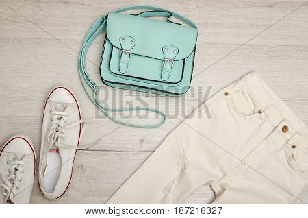 White Jeans And Sneakers, Mint Bag. Fashionable Concept. Wooden Background.