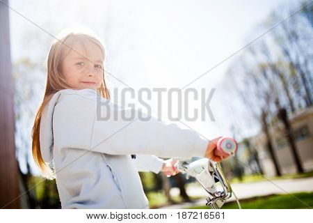 Portrait of girl with bicycle rudder in afternoon on sky background