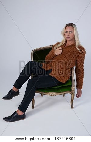 Full length of transgender looking away while sitting on chair against gray background