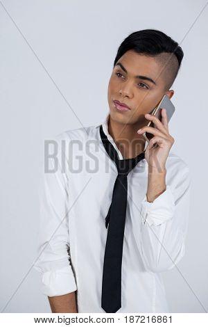 Transgender female using smart phone while standing against white background