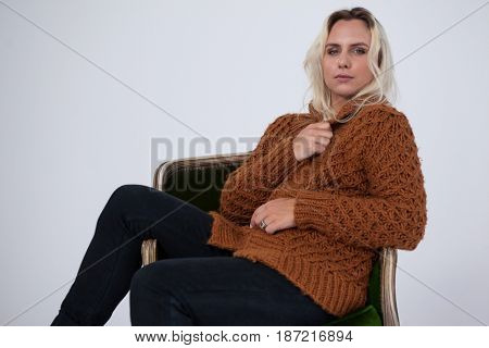 Transgender woman sitting on chair over gray background