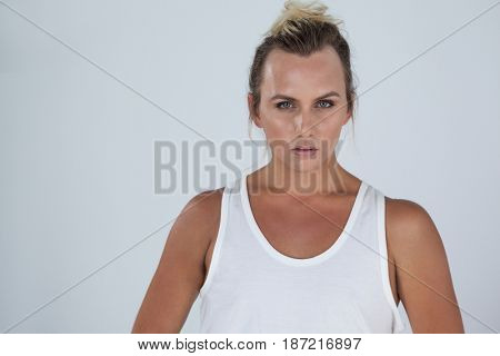 Portrait of beautiful transgender woman standing over gray background