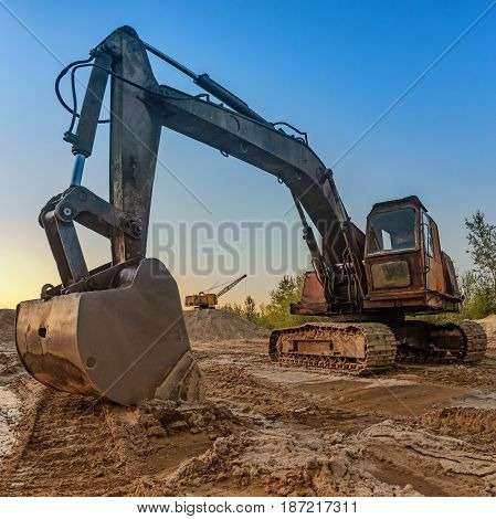 The old excavator with a large bucket extracts sand in a quarry. Ukraine