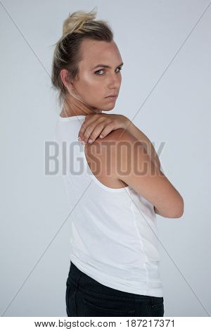Portrait of beautiful transgender woman looking over shoulder against gray background
