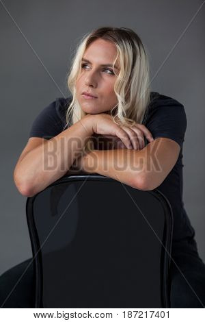 Thoughtful transgender woman leaning on chair against gray background
