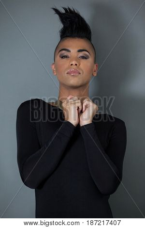 Portrait of confident transgender with half shaved hairstyle standing against gray background