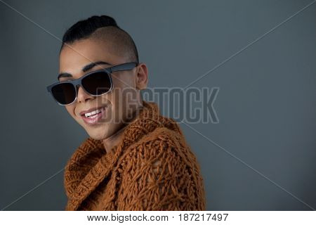 Portrait of smiling transgender woman wearing sunglasses against gray background