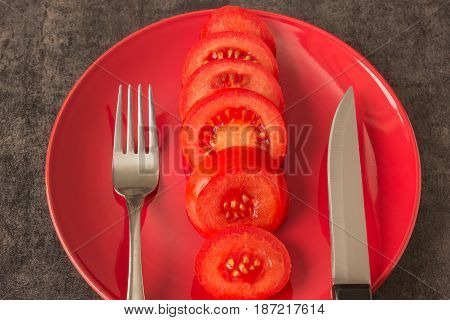 Tomato on the plate red. Fork and knife. Concept - vegetarianism weight control diet healthy eating.