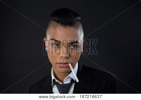 Transgender woman with cigarette in mouth over black background