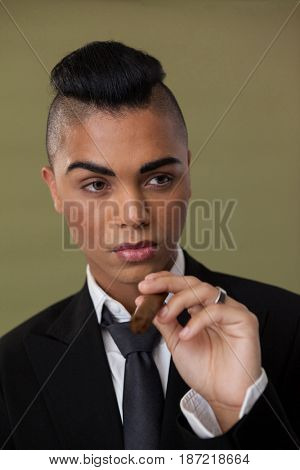 Close up of transgender woman holding cigarette on green background