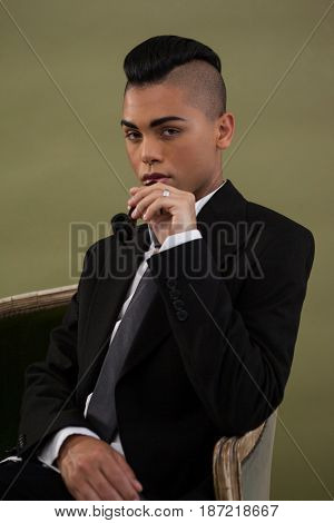 Portrait of transgender woman holding smoke pipe while sitting on chair against green background