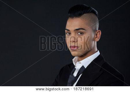 Portrait of transgender woman standing against black background
