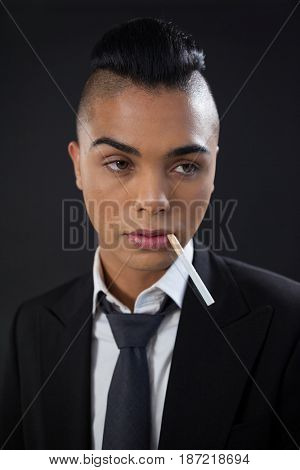 Transgender with cigarette in mouth against black background