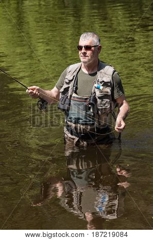 A fisherman with a pole hunts trout. A handsome man flying on the river Otava South Bohemia Czech republic.
