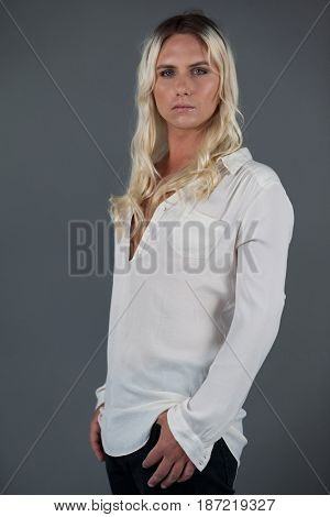 Portrait of transgender woman standing against gray background