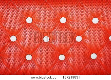 Close up diamond cushion pattern with button of orange vintage sofa texture and background