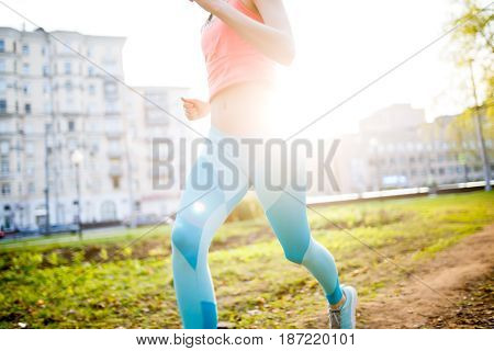 Sports woman on morning run in park on background of houses