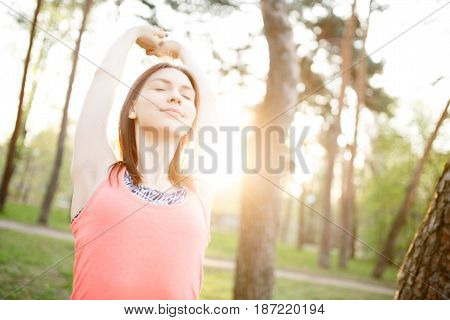 Sports brunette doing stretching exercises in morning park . Sunflare effect