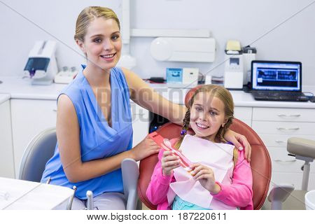 Portrait of smiling mother and daughter at dental clinic