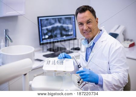 Portrait of smiling dentist holding dental hand piece in clinic
