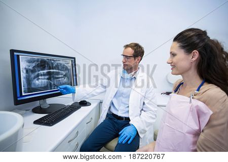 Dentist showing an x-ray of teeth to female patient at dental clinic