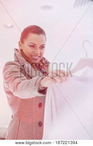 Happy young woman choosing sweater in store