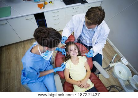 Dentists examining a young patient with tools in dental clinic