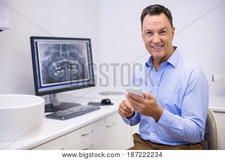 Portrait of happy dentist using mobile phone in clinic