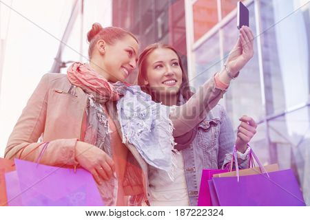 Female friends with shopping bags taking self portrait through mobile phone