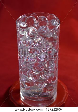 Silicone balls on a red background in a glass with backlight