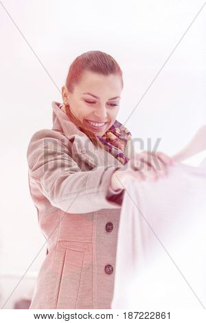 Happy young woman looking sweater in store