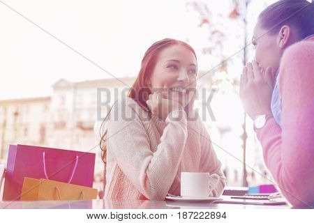 Happy female friends gossiping at outdoor cafe