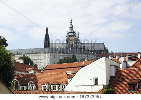 View to part of Prague Castle with the Sct. Vitus Church spires and part of the President Castle in front. In the foreground the old Houses with their typical red tile roofs.