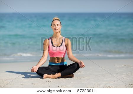 Full length of young woman meditating in lotus position at beach